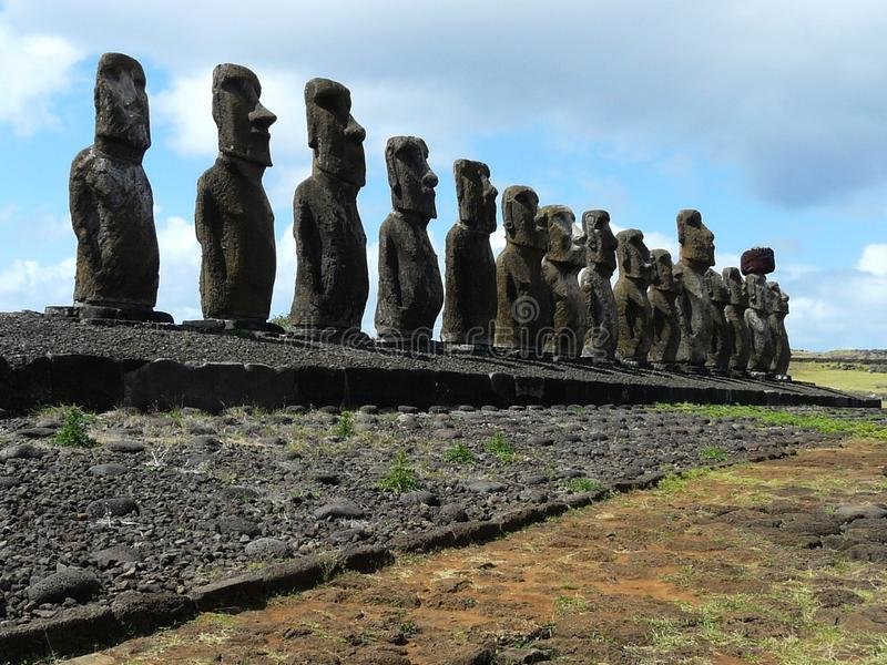 Moai parade on Easter Island, Chile. Parade of mysterious unique statues moai on the ceremonial platform of the archaeological site of Easter Island Ahu stock photography