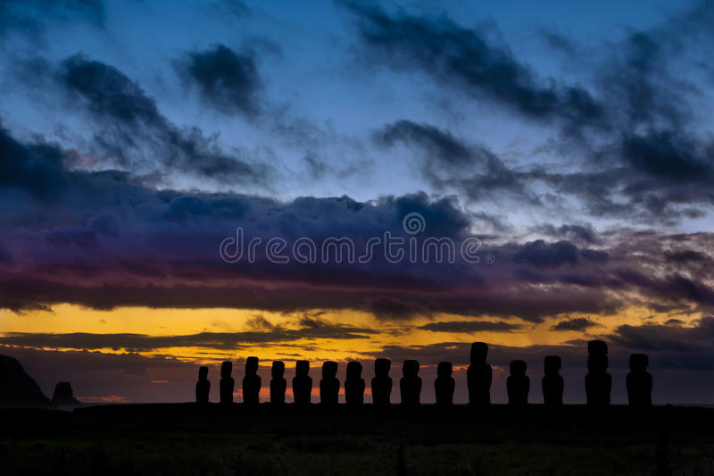 Moai quinze contre le lever de soleil orange et bleu image stock