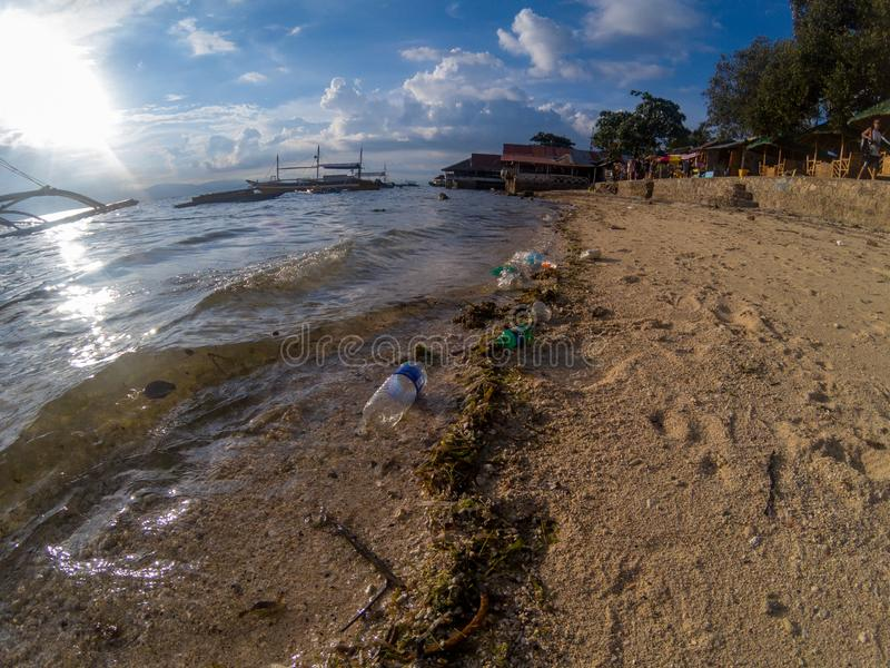 Moalboal, the Philippines - plastic trash on sea beach. Human impact on ocean pollution. Plastic garbage by seaside royalty free stock photography