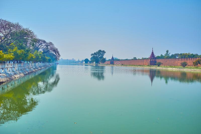 The moat of Mandalay Palace, Myanmar. The wide doug moat of Mandalay Palace and its walls with watching towers on its bank, Myanmar royalty free stock photo