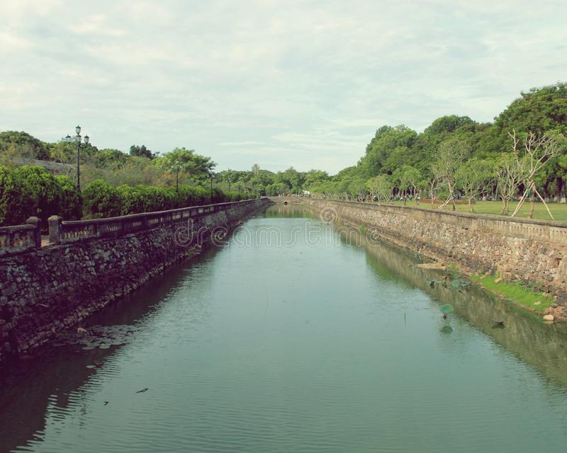 Moat Waterway by the Imperial City. A long shot of the moat waterway that surrounds the old imperial city in Hue, Vietnam. The barriers are brick, with trees royalty free stock photos