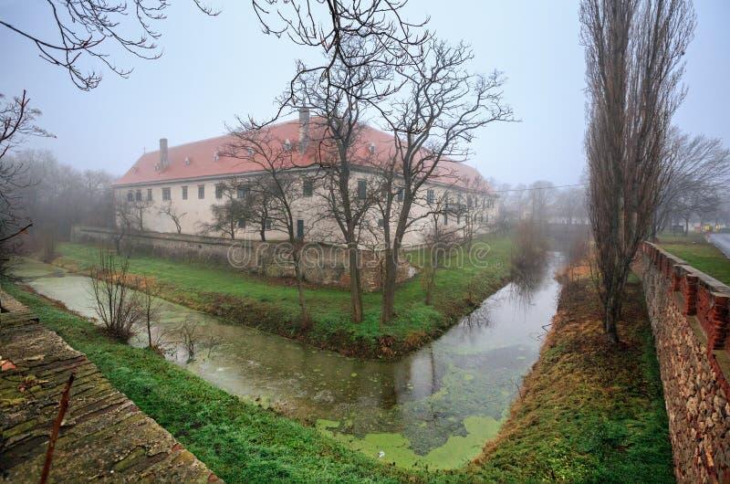 Moated rezydencja ziemska dom w targowym miasteczku Guntersdorf na mgłowym zima dniu Niski Austria zdjęcia stock
