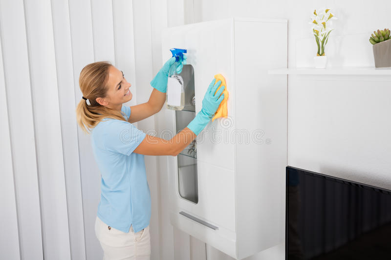 Mobília da limpeza da mulher em casa imagens de stock