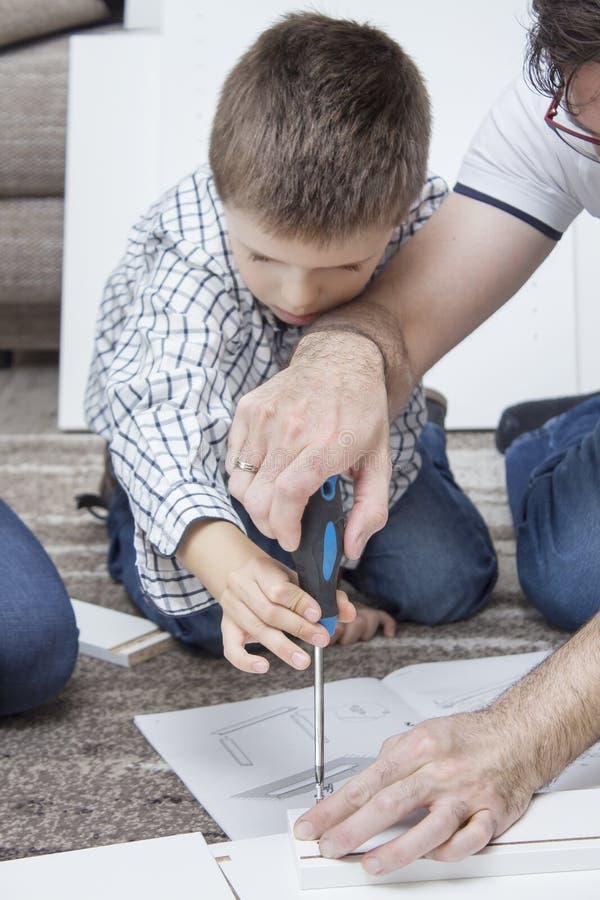 Mobília da torção do pai e do filho O menino está guardando uma chave de fenda e o pai ajuda a parafusar o parafuso fotografia de stock
