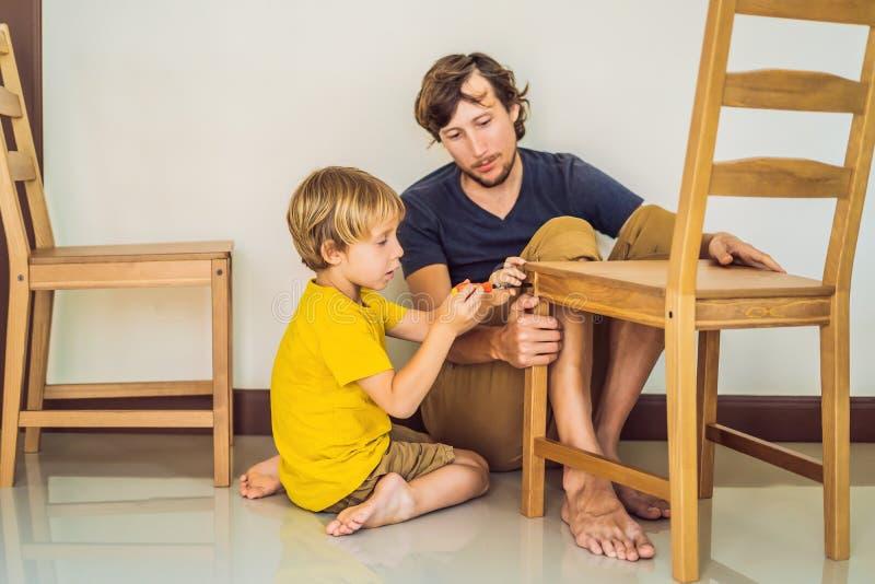 Mobília de montagem do pai e do filho Menino que ajuda seu paizinho em casa Conceito de família feliz fotos de stock