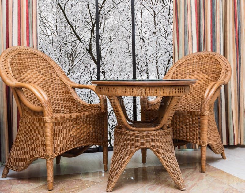 Mobília do Rattan perto da janela com uma paisagem do inverno foto de stock