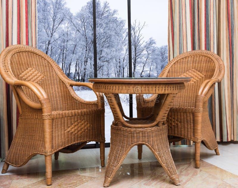Mobília do Rattan perto da janela com uma paisagem do inverno imagens de stock