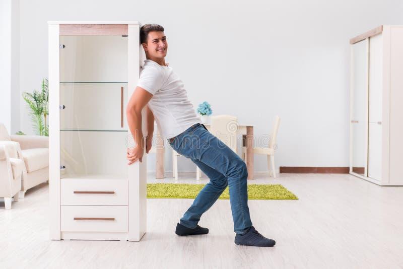 A mobília movente do homem em casa imagem de stock royalty free