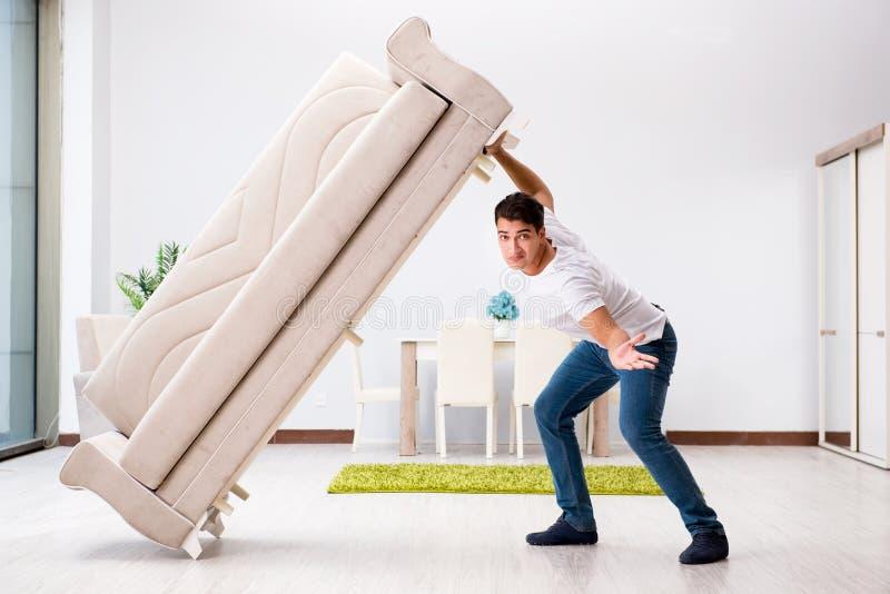 A mobília movente do homem novo em casa foto de stock