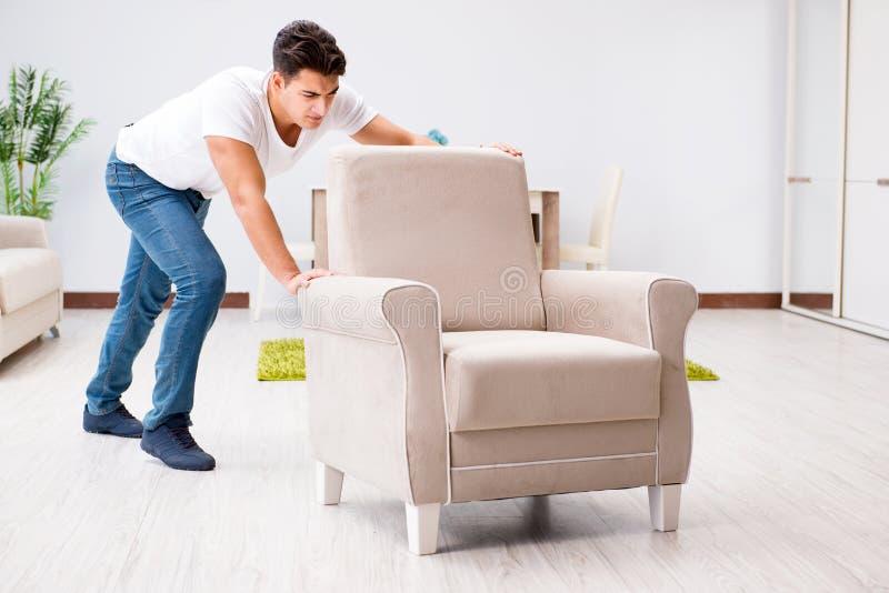 A mobília movente do homem novo em casa foto de stock royalty free