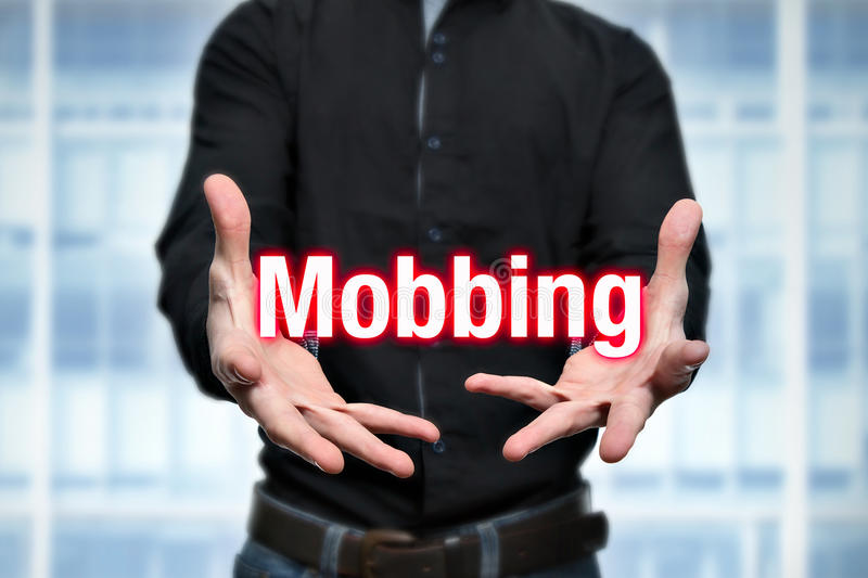 Mobbing, bullying, man holds lettering in the hands royalty free stock photography