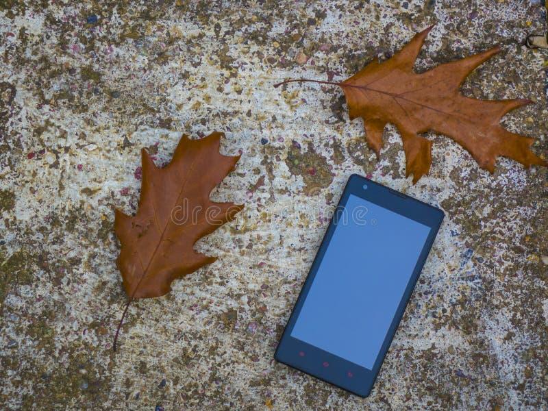 Mobiel in aard op een rotsachtige textuur stock afbeelding
