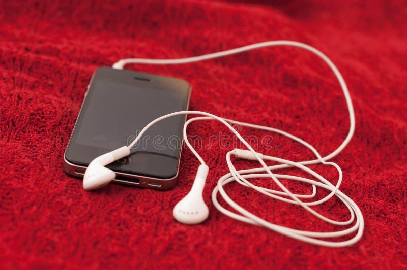 Mobiele de celtelefoon van Smartphone met hoofdtelefoons royalty-vrije stock fotografie