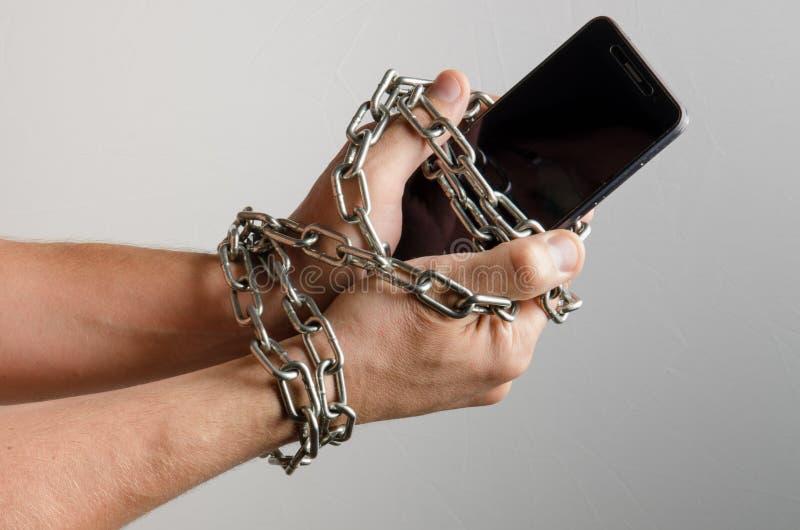 Mobiele die telefoon aan de handen van een mens, telefoonafhankelijkheid wordt geketend royalty-vrije stock foto