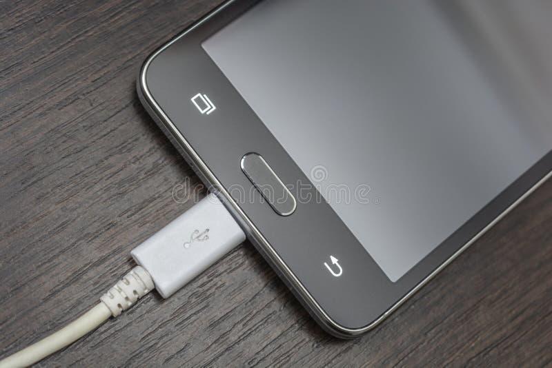 Mobiele slimme telefoons die op houten bureau laden stock afbeeldingen