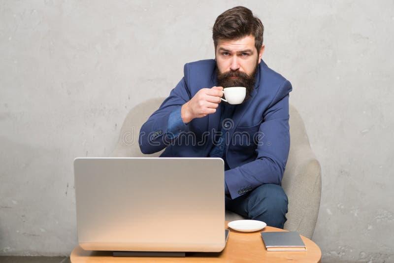 In mobiele stijl Gebaarde mens van zijn hete drank genieten en mobiel Internet die Zakenman met mobiele apparaat het drinken thee stock afbeelding