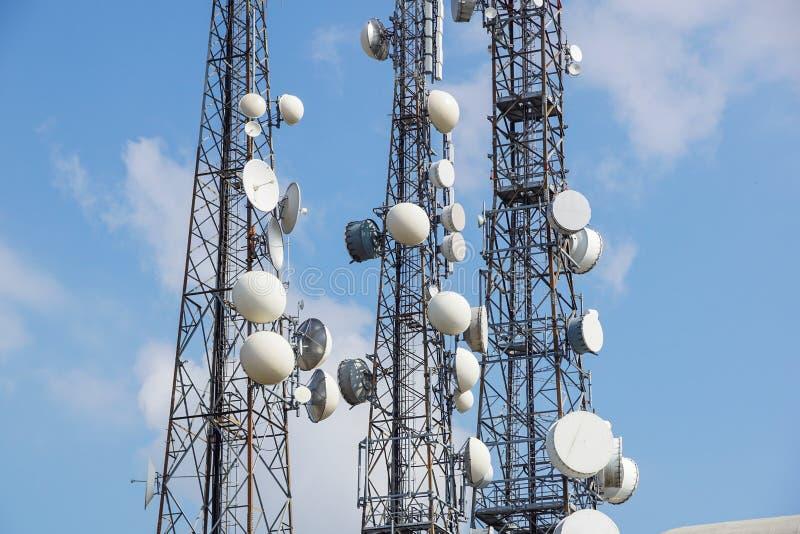 Mobiele telefoon communicatie antennetoren met satellietschotel op blauwe hemelachtergrond, Telecommunicatietoren stock fotografie