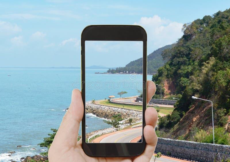 Mobiele telefoon die landschap van krommeweg en overzees tonen van de heuvel toneelpunt van Nang Phaya in Thailand stock foto's