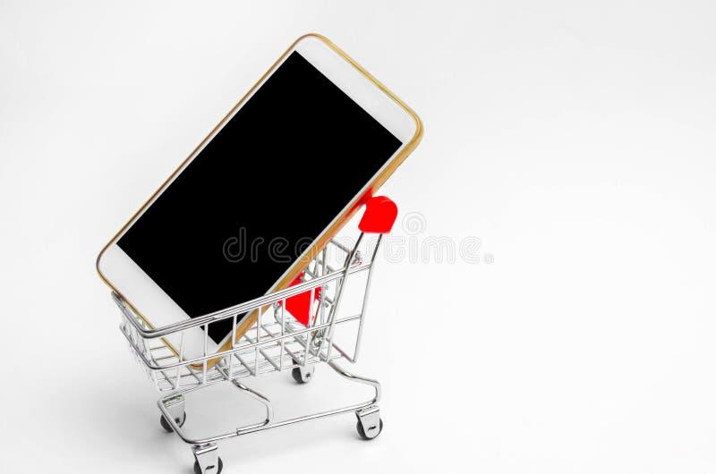 Mobiele telefoon in een supermarktkarretje het kopen van en het verkopen van een smartphone Online opslag consumentenkrediet Geïs royalty-vrije stock fotografie