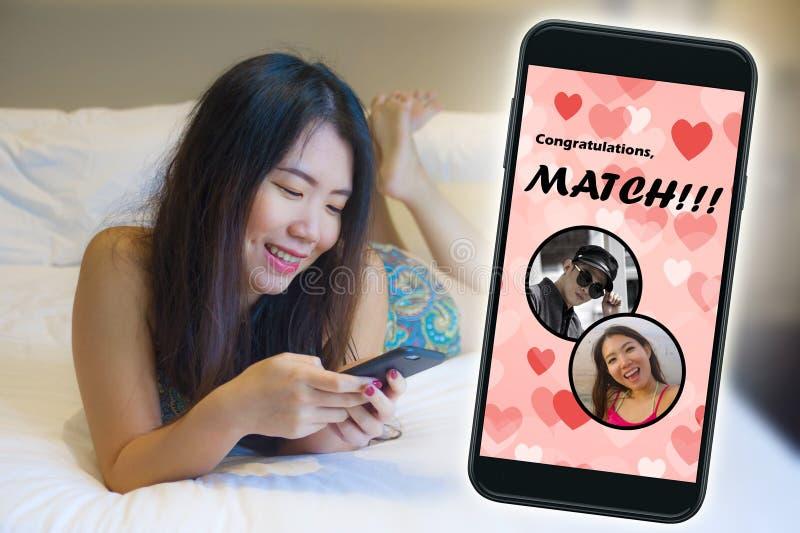 Mobiele telefoon en jong mooi en gelukkig Aziatisch Chinees meisje die het online vrolijk dateren app gebruiken ontvangend een ge stock foto's