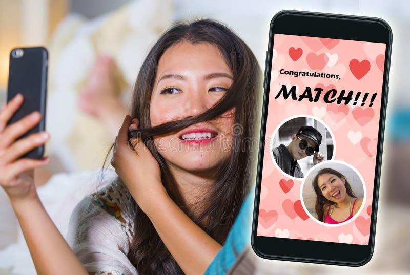 Mobiele telefoon en jong mooi en gelukkig Aziatisch Chinees meisje die het online vrolijk dateren app gebruiken ontvangend een ge royalty-vrije stock afbeeldingen