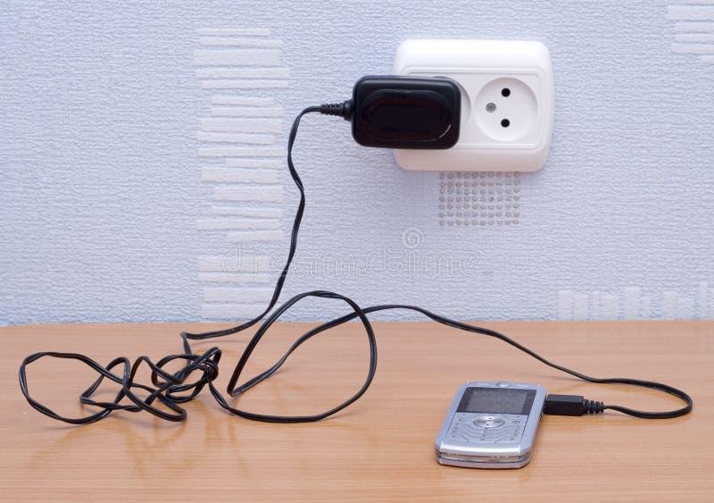 Mobiele telefoon en lader stock foto