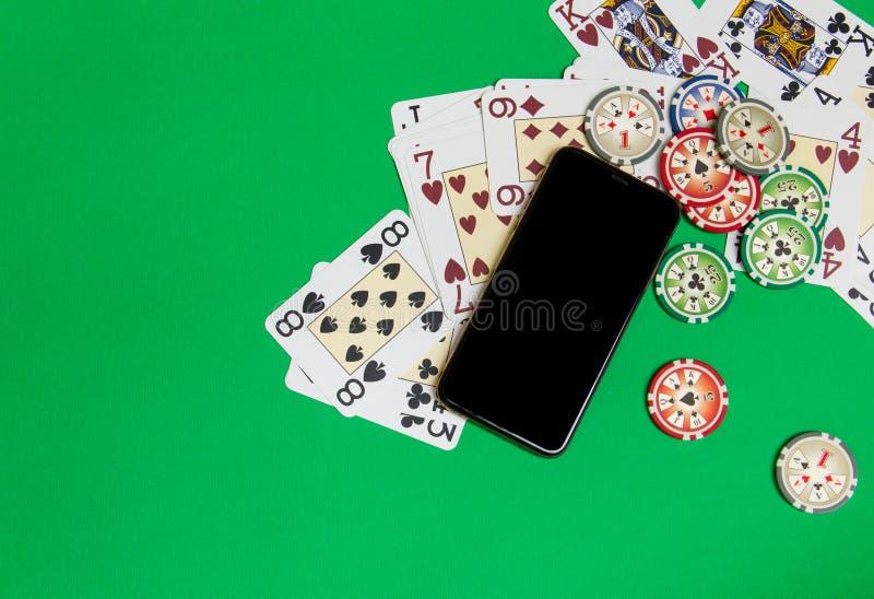 Mobiele telefoon en pookspaanders met speelkaarten op een groene lijst Online casinoconcept stock afbeeldingen