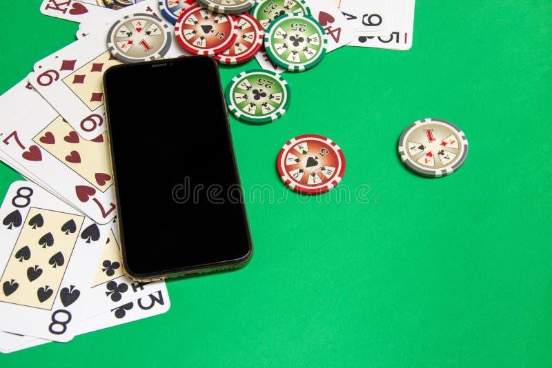 Mobiele telefoon en pookspaanders met speelkaarten op een groene lijst Online casinoconcept stock afbeelding