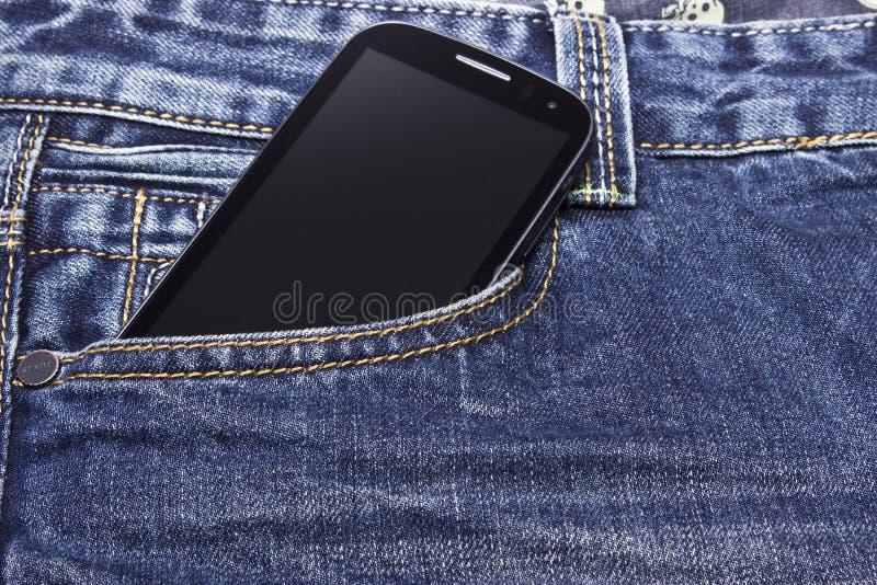 Mobiele telefoon in jeans stock afbeelding