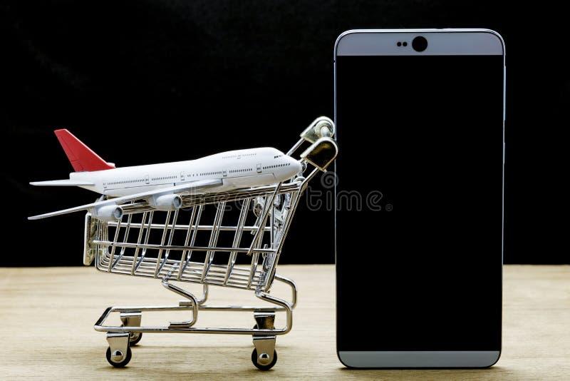 mobiele telefoon met vliegtuigmodel en boodschappenwagentje op hout, Onli stock fotografie