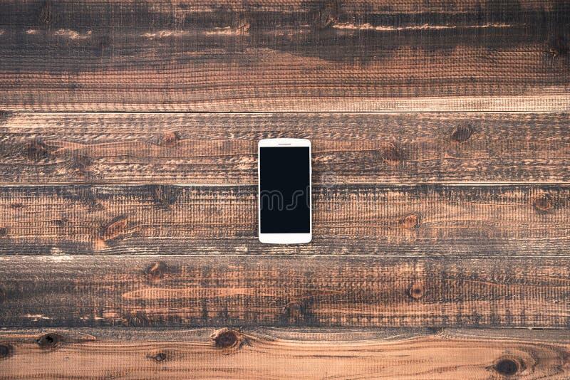 Mobiele telefoon op het houten bureau stock foto