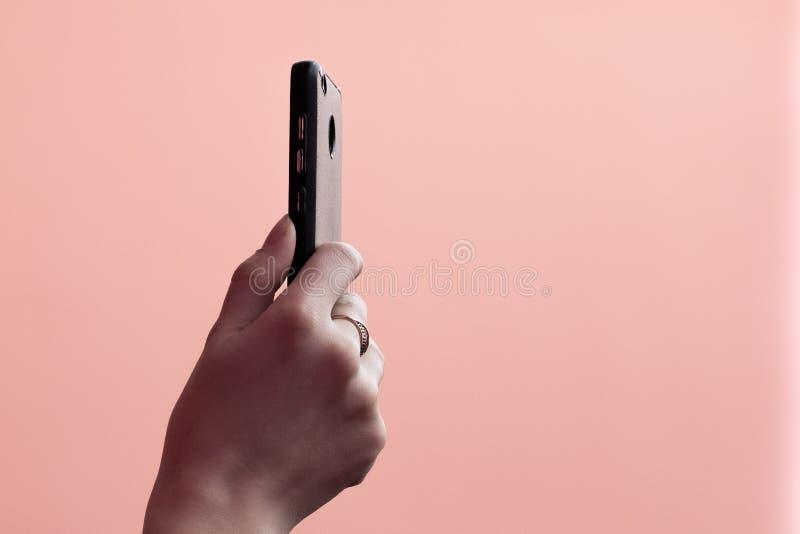 Mobiele telefoon in vrouwelijke hand Gouden ring op de vinger Leef rapport of het schieten op smartphone Roze achtergrond Modern  stock fotografie