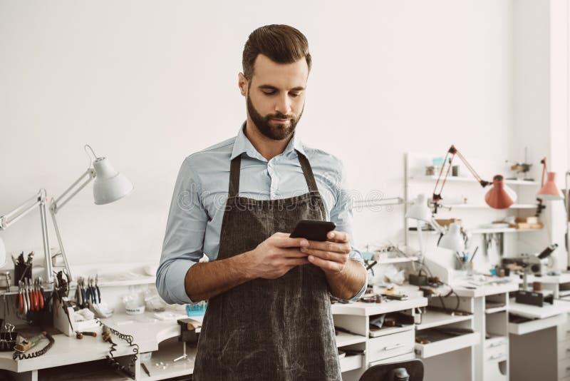 Mobiele toepassing voor het werk Sluit omhoog portret van jonge mannelijke juwelier in schort die een smartphone houden en in mob stock foto