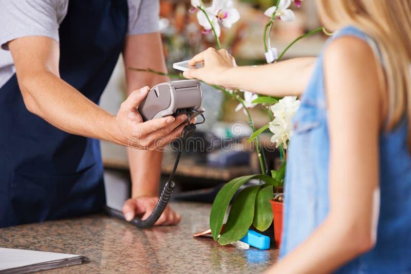 Mobil betalning på kontrollen i detaljist royaltyfri bild