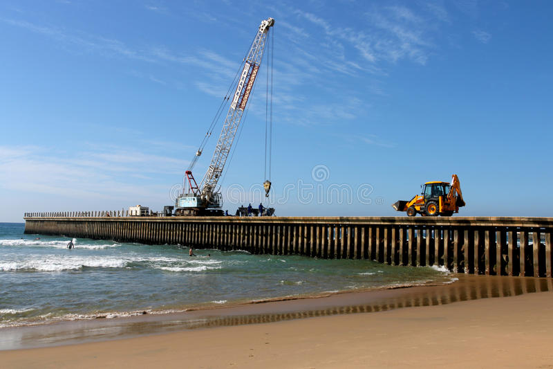Mobil Crane And Pay laddare på Pier Construction Site royaltyfri bild
