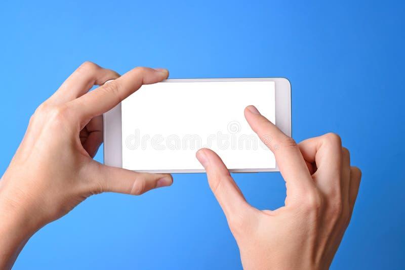 Mobil för handinnehavtelefon och rörande skärm som isoleras med kopieringsutrymme på blå bakgrund arkivfoton