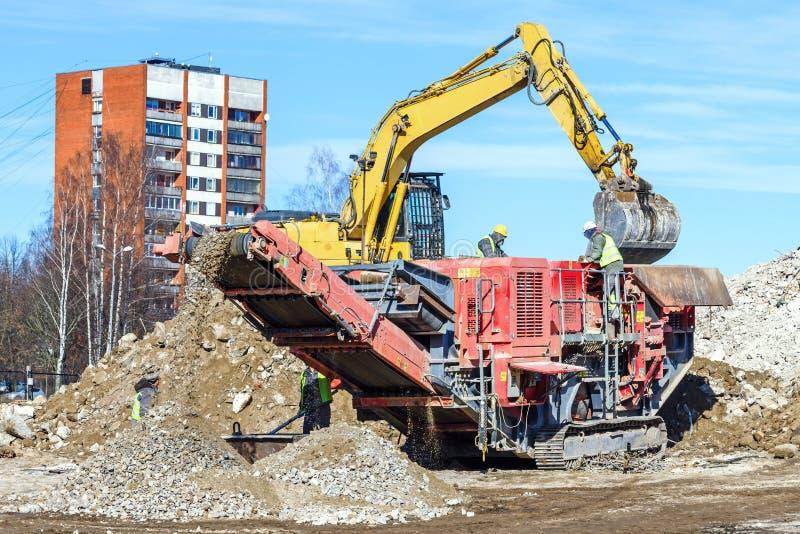 Mobil kross för crawlsimmare och grävskopaCrushing betong arkivbild