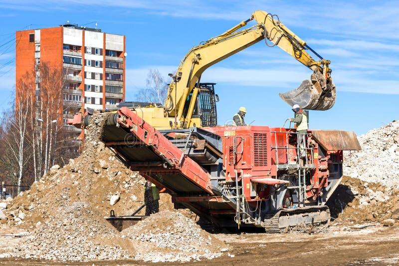 Mobil kross för crawlsimmare och grävskopaCrushing betong royaltyfria bilder