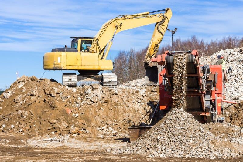 Mobil kross för crawlsimmare och grävskopaCrushing betong royaltyfri bild
