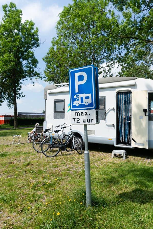 Mobil parkeringsplats med blå trafikskylt fotografering för bildbyråer