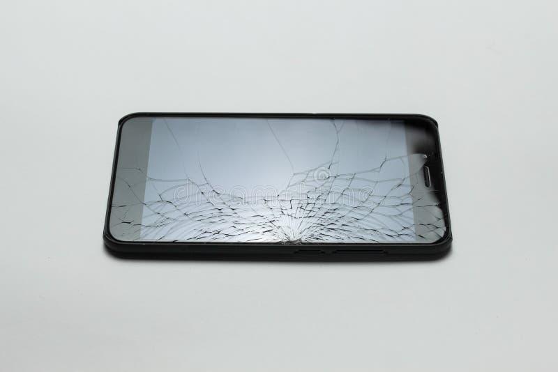 Mobil smartphone med den brutna skärmen på vit bakgrund royaltyfri fotografi