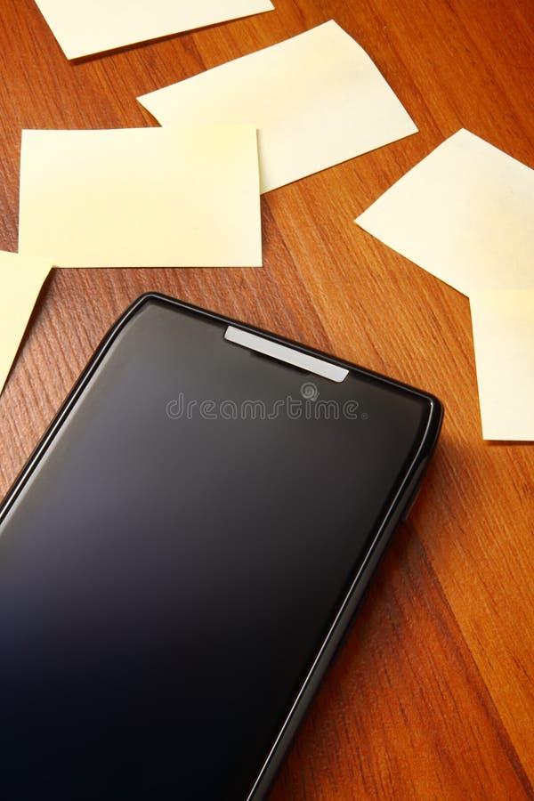 Mobil telefon med postits royaltyfri foto