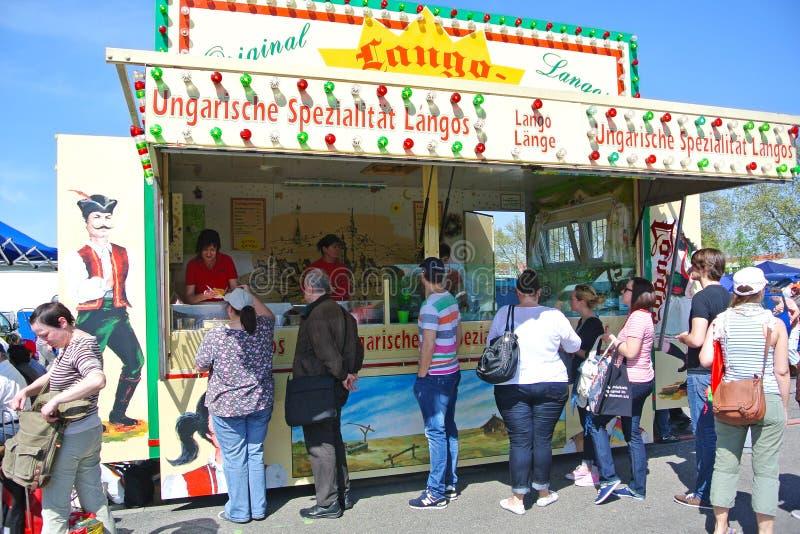 Mobil utomhus- matställning med traditionell ungersk mat som kallas 'Lángos på nöjesplats under stor årlig loppmarknad royaltyfri foto