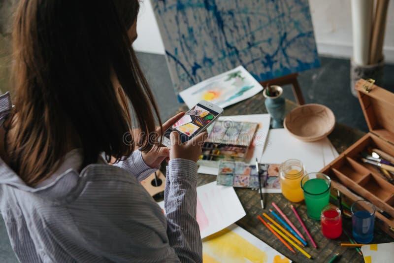 Mobila foto av konst Konstnär som tar foto av hennes pauntings Utrymmeskrivbord för idérikt arbete royaltyfri foto