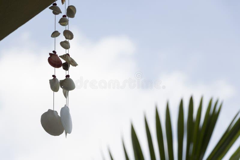 Mobile accrochant de carillon de vent de coquillage sur le fond de ciel images stock