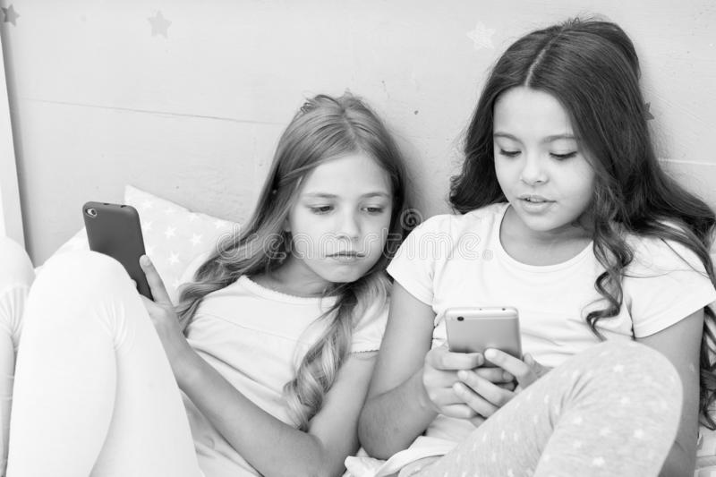Mobile addicted. Girl play games smartphone online. Pajamas party concept. Happy childhood. Kids surfing internet mobile royalty free stock photo