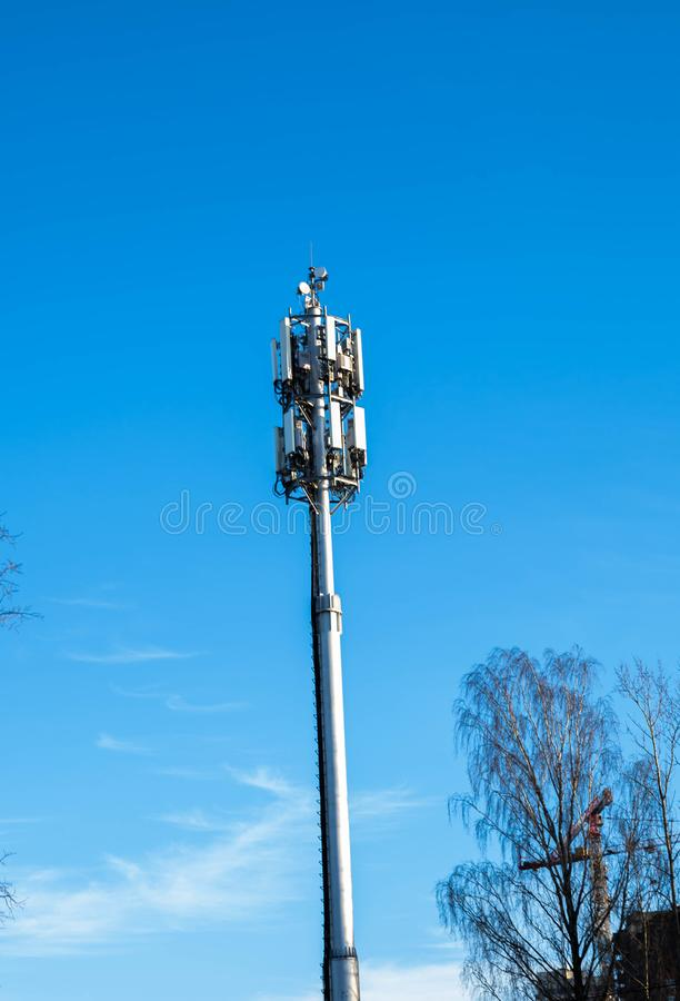 Mobile antenna in the city against the blue sky. Tower telephone broadcast broadcasting communication equipment metal network radio satellite station technology royalty free stock images