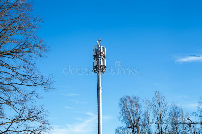 Mobile antenna in the city against the blue sky. Tower telephone broadcast broadcasting communication equipment metal network radio satellite station technology stock images