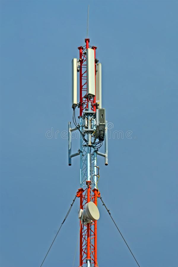 Mobile antenna tower on blue sky, modern transmitter diversity,. Mobile antenna tower closeup on blue sky in sunny day, modern transmitter diversity royalty free stock photo