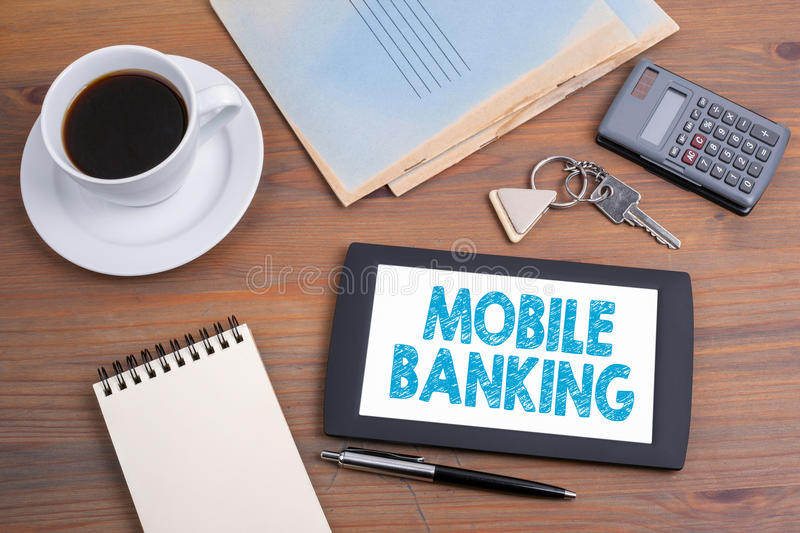 Mobile banking, business concept. Text on tablet device on a wooden table.  royalty free stock photo